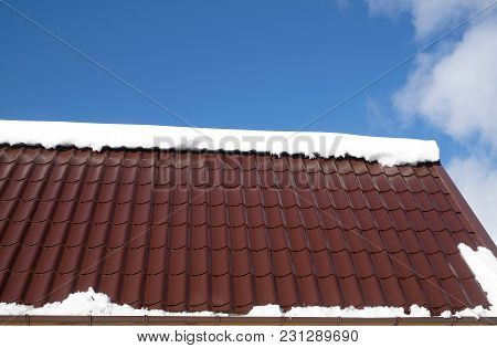 Side Of Country House Roof From Brown Metal Tile With Snow Heap In Sunny Spring Day Under Blue Sky W