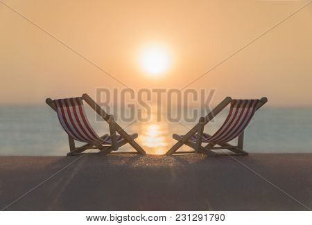 Two Striped Red-white Sunbeds At Sandy Tropical Sunset Ocean Beach. Natural Travel Background. Touri