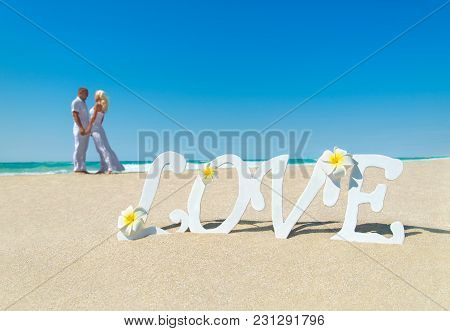 Loving Couple At Tropical Ocean Sandy Beach With Love Word Decoration And Frangipani Flowers. Propos