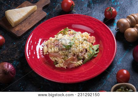 Italian pasta with cheese sauce and slices of prosciutto smoked ham