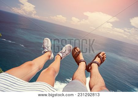 Man In Sandals And Woman In Sport Shoes Sitting Above The Ocean