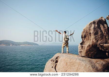 Cheerful Traveler Standing On The Rocks Near The Ocean