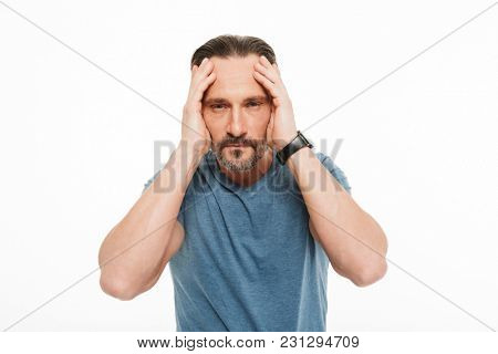 Portrait of an exhausted mature man dressed in t-shirt holding hands on his head isolated over white background