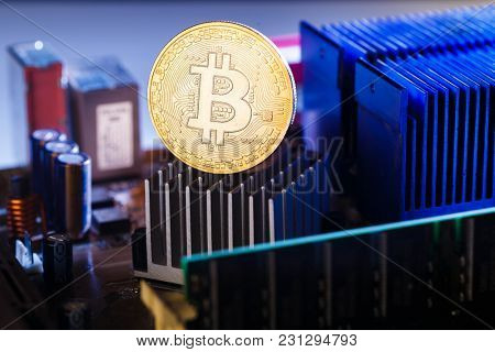 Photo of bitcoin and processor on dark background