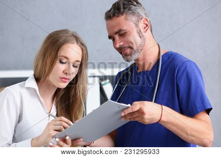 Handsome Mature Doctor Offer Pad Sign With Silver Pen Portrait. Physical Agreement Form Signature Di