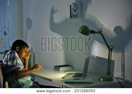 Scared African American boy with laptop in dark room. Cyber bullying