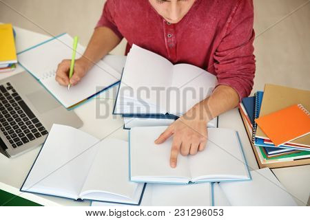 Male student preparing for exam at table