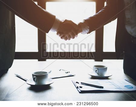 Two Businessmen Shaking Hands During A Business Lunch.