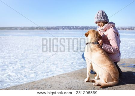 Woman with cute dog near river on winter day. Friendship between pet and owner