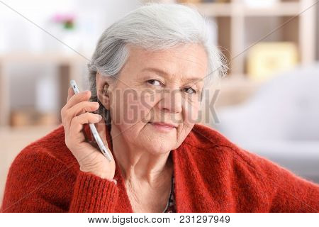 Mature woman with hearing aid talking on phone indoors