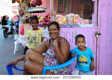 La Romana, Dominican Republic - 02 December 2017: Laughing Woman Selling Vegetables And Fruits With
