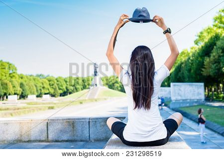 Young woman holding a blue hat above the head while sitting in the park in summer