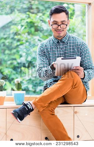 Young Asian man wearing casual clothes while browsing the internet on a tablet PC in the office during break