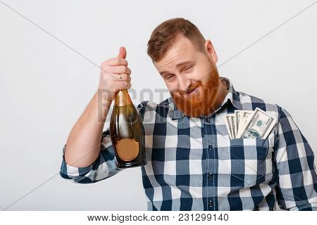 Drunk Bearded Man Drinks Champagne From A Bottle And Celebrates A Cash Win