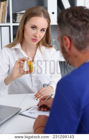 Beautiful Smiling Female Patient Hold In Arms Jar Of Pills Portrait While Doctor Write Recipe. Panac