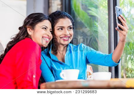 Customers in Indian cafe taking selfie, view through shop window