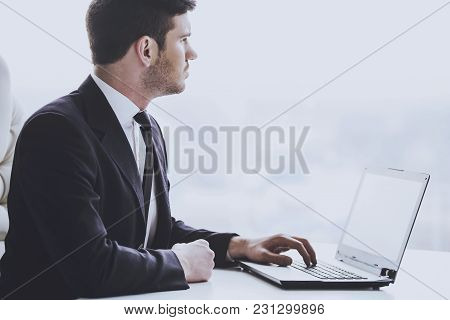 Side View Of Young Businessman Is Working With Laptop In Office.