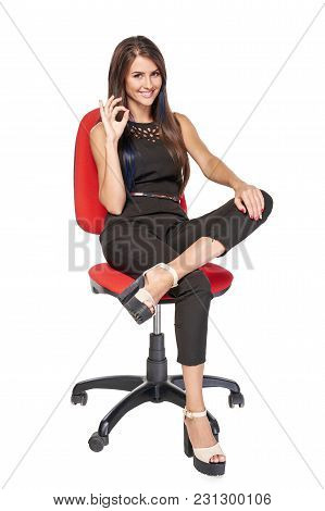 Smiling Woman In Black Sitting On Office Chair Smiling At Camera Gesturing Ok, Full Length Portrait