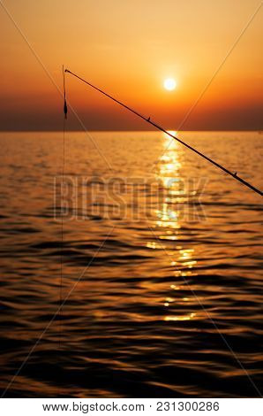 Fishing Pole With Sun Setting Over Sea In The Background