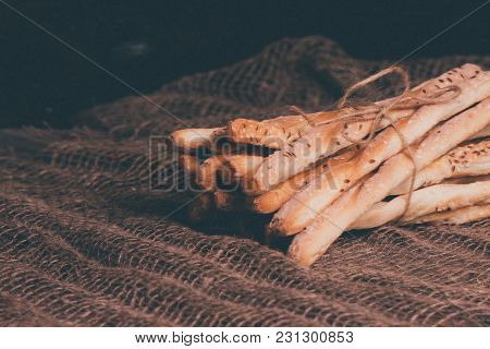 Delicious Breadsticks Grissini. Italian Appetizers. Wooden Dark Background And Burlap
