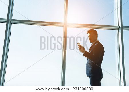 Side View Of Young Businessman Is Standing Near A Panoramic Window And Looking At The Phone.