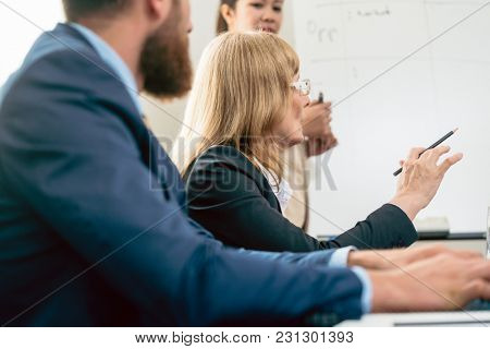 Side view of a middle-aged business woman presenting her vision and opinion about a project during a decision-making meeting in the conference room