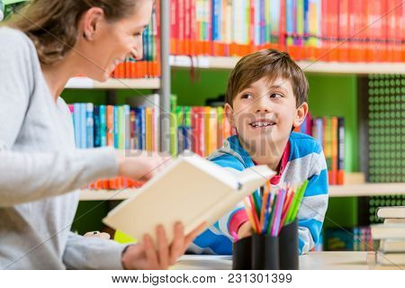 Mother reading book from library to her son turning a page