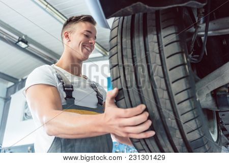 Low-angle view of the hand of a skilled auto mechanic holding a new high-quality tire during work in a modern automobile repair shop