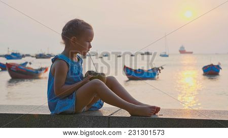 Little Cute Girl Drinks Coconut Water With Drinking Straw At Seafront With The Sea And Fishing Boats