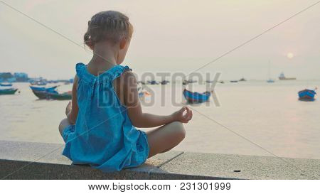 Little Cute Girl Meditates In Turkish Pose At Seafront With The Sea And Fishing Boats On The Backgro