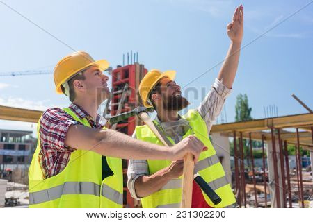 Confident and determined young worker pointing up while imagining with his colleague the height of a building under construction
