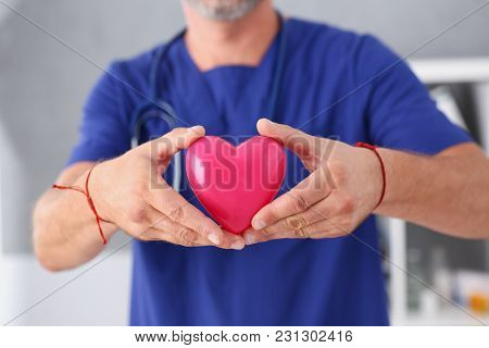 Male Doctor Wearing Blue Uniform Hold In Arms Red Toy Heart Closeup. Cardio Therapeutist Student Edu