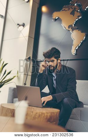Businessman Working On A Laptop Computer And Having A Phone Conversation In A Modern Office