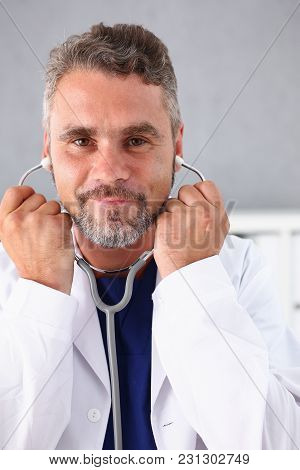 Handsome Mature Smiling Male Doctor Hold In Arms Stethoscope Going To Listen Patient. Tool Shop Or S
