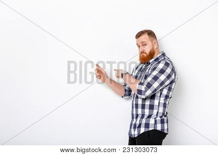 Handsome Man With Beard Pointing Copy Space. Young Man In Plaid Shirt Looking At Camera And Pointing