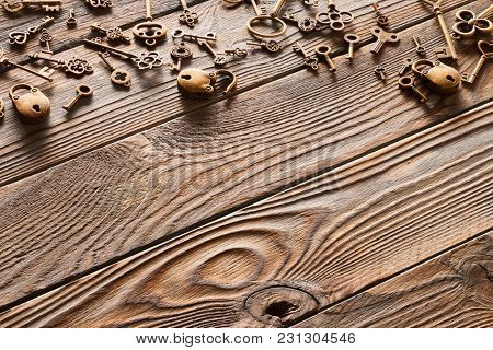 Various metal keys and locks over wooden background