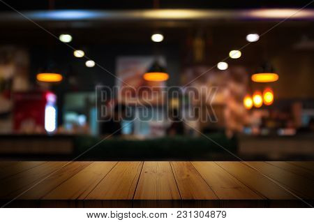 Empty Wooden Table Top With Blur Coffee Shop Or Restaurant Interior Background.