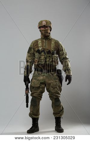 Full-length image of soldier in camouflage with gun