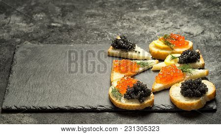 Sandwiges With Red Salmon Caviar And Black Stugeon Caviar On A Black Stone Board On A Black Table, T