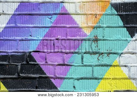 Abstract Detail Of Brick Wall With Fragment Of Graphic Graffiti. Urban Art Close-up, For Background