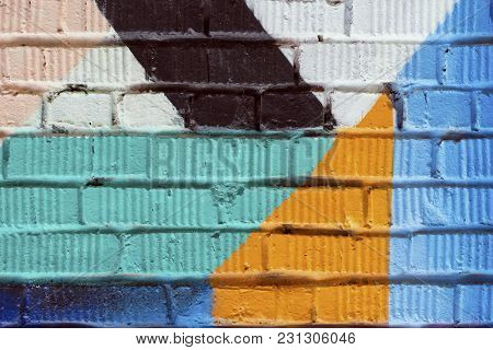 Abstract Detail Of Brick Wall With Fragment Of Blue, Red Graffiti. Urban Art Close-up, For Backgroun