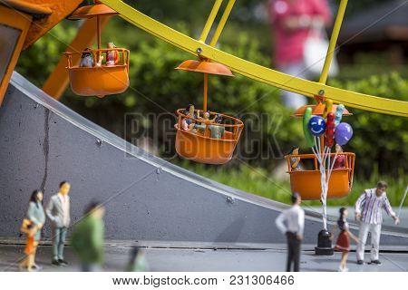 Miniature Carnival And Ferris Wheel. Miniature Men Painted In Colorful Colors. Diorama.