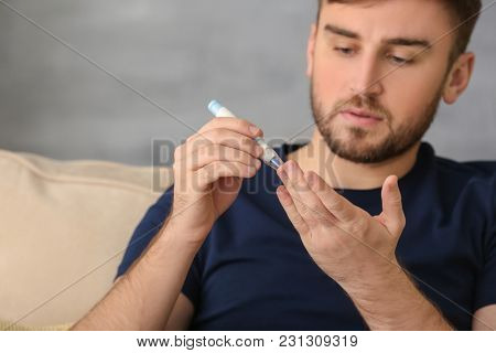 Diabetic man taking blood sample with lancet pen at home