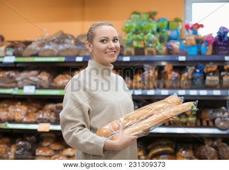 Portrait of young woman with bread in shop. Small business owner