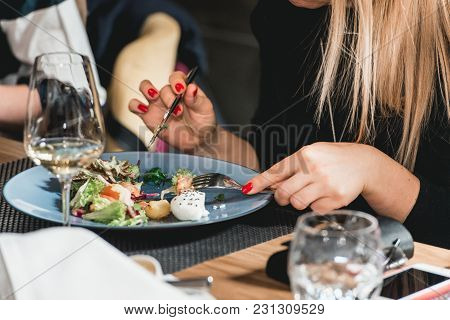 Blond Woman Eats Delicious Salmon Salad With Egg In A Restaurant At The Food And Wine Pairing. Small