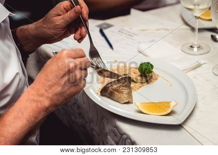Man Eats Portion Of Delicious Fish Fillet In Sauce At The Restaurant. Small Portion On A White Plate