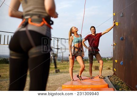 Instructor Man Guiding Woman On Rock Climbing Training Wall. Healthy Lifestyle And Leisure Concept.
