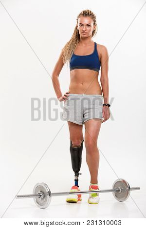 Full length portrait of a young disabled sportswoman doing exercises with a barbell isolated over white background