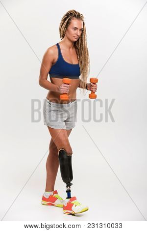 Photo of gorgeous strong young disabled sports woman with prosthesis standing isolated over white background. Looking aside make exercises with dumbbells.