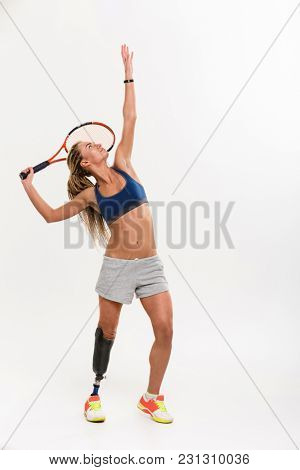 Image of young disabled sports woman tennis-player with prosthesis isolated over white background. Looking aside.